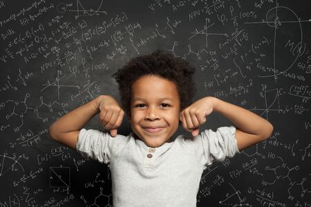 Cute black child student boy on chalkboard background with science formulas