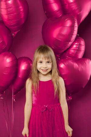 Adorable girl with pink balloons on vibant pink background