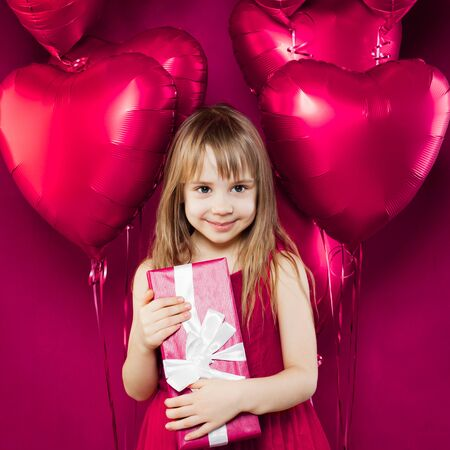 Happy little child girl with gift and pink balloons on colorful pink background Фото со стока