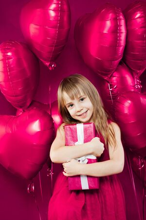 Birthday girl portrait. Child holding gift on pink balloons background Imagens