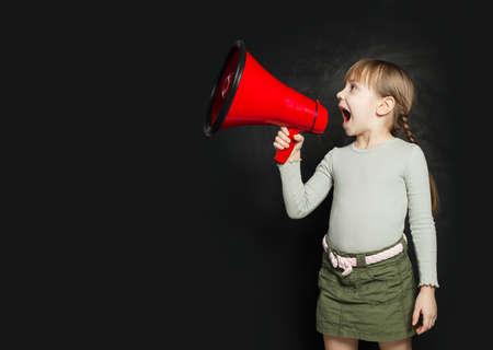 Funny little girl screaming loudly through a megaphone against a blackboard. Kid with loudspeaker Zdjęcie Seryjne