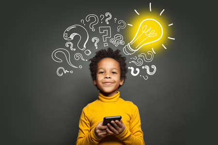 Black child using smartphone with lightbulb on blackboard background. Advance learning concept