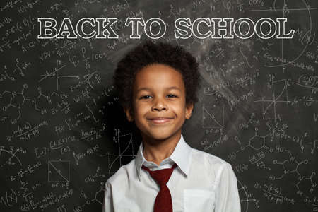 African American school child student on blackboard background with science and maths formulas. Back to school concept