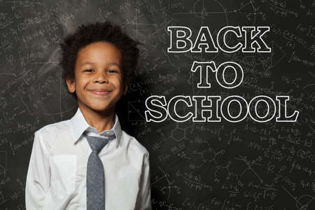 Happy smart African American child student with chalk science formulas blackboard background, back to school concept