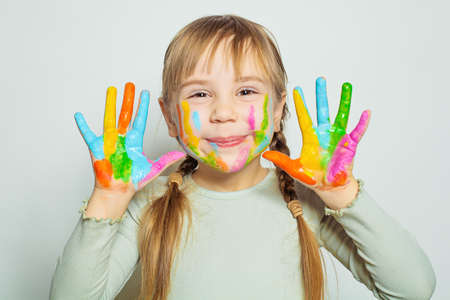 Happy smiling child girl art school student showing her colorful painted hands on white. Girl drawing Zdjęcie Seryjne
