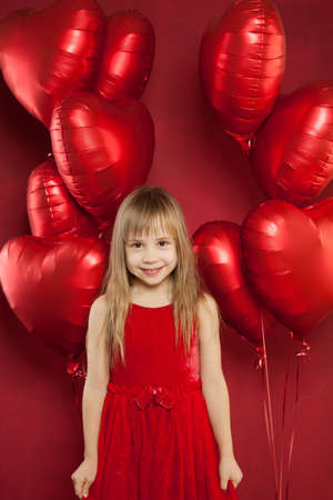Cheerful happy child girl smiling on red
