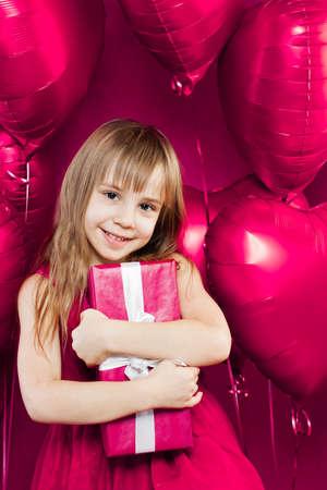 Pretty child girl holding gift on colorful pink background Zdjęcie Seryjne