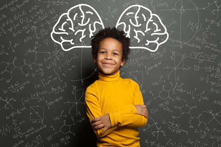 Smiling black child with big brain and science formulas on black, education and brainstorming concept