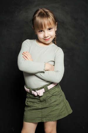 Cute kid child girl on blackboard background Zdjęcie Seryjne