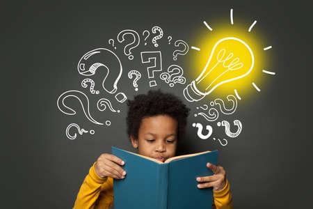 Intelligent black kid student reading book and having idea. Brainstorming and idea concept Zdjęcie Seryjne