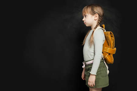 Sad school child girl standing with backpack on black. School problem concept