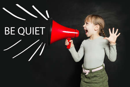 Be quiet concept. Funny little girl screaming loudly through a megaphone Be quiet!
