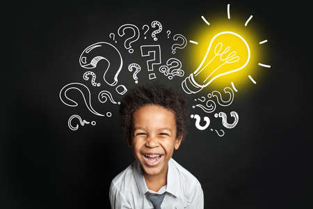 Lightbulb, question marks and smart laughing child. Brainstorming and idea concept Zdjęcie Seryjne - 151408015