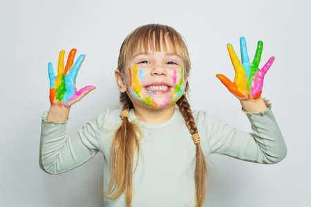 Happy girl drawing and showing her colorful painted hands on white background portrait