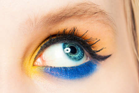 Woman eye looking up. Blue and yellow eyeshadow and black eyeliner arrow make up close up Zdjęcie Seryjne - 151408020