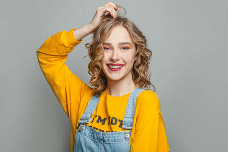 Cute young woman smiling on gray background Zdjęcie Seryjne