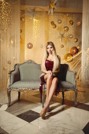 Perfect woman with long blonde hair sitting on luxurious vintage sofa