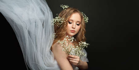 Young woman holding white flowers on black background