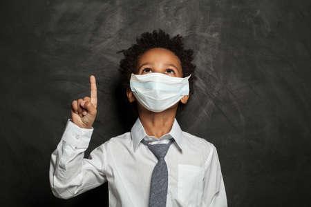 Black kid boy in medical protective face mask pointing up on blackboard background Zdjęcie Seryjne