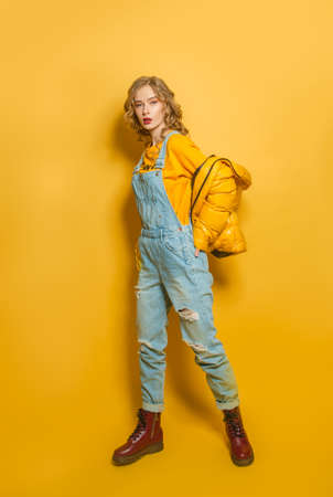 Fashion woman in down jacket and denim jumpsuit on bright yellow background