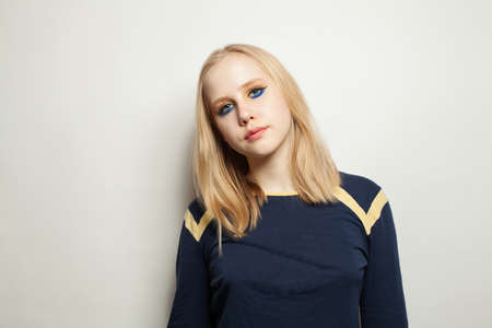 Teenager girl with makeup wearing blue longsleeve on white background
