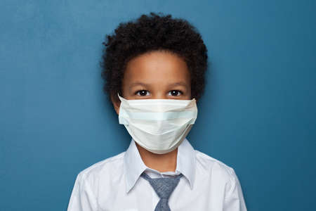 Black child boy student in medical protective face mask on blue background