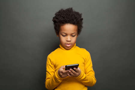 African American child holding smartphone and playing Stock Photo