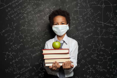 Happy child in medical protective face mask holding books and green apple on blackboard background