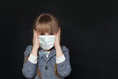 Unhappy child girl in medical protective face mask covering her ears