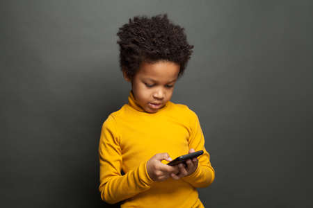 Small black child playing with smartphone Stock Photo
