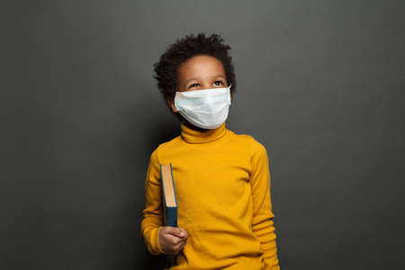 Happy black child boy in medical protective face mask on blackboard background