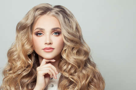 Blonde woman with long healthy curly hair on white background