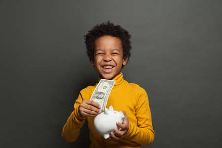 Laughing black child with money box and one us dollar on blackboard background Zdjęcie Seryjne