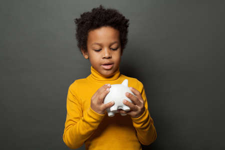African American child looking at money box on blackboard background