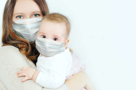 Little baby and mother in medical protective face mask on white background Zdjęcie Seryjne