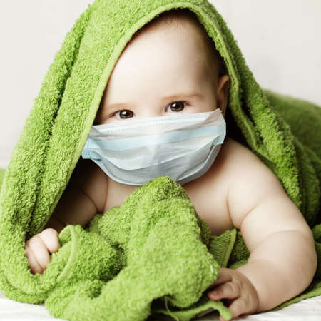 Cute little baby in medical protective face mask