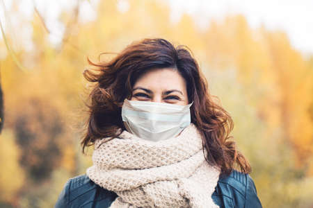 Autumn woman in medical protective face mask walking outdoors, fall season portrait