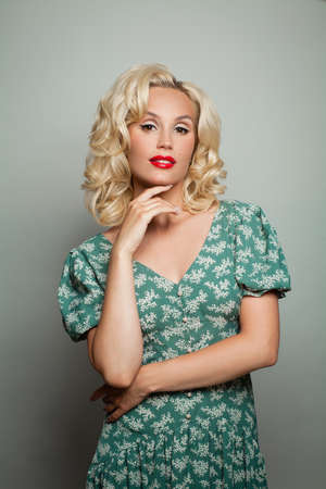 Romantic blonde woman with healthy curly haircut and makeup standing on white Zdjęcie Seryjne