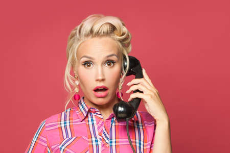 Shocked pinup woman phone on red background