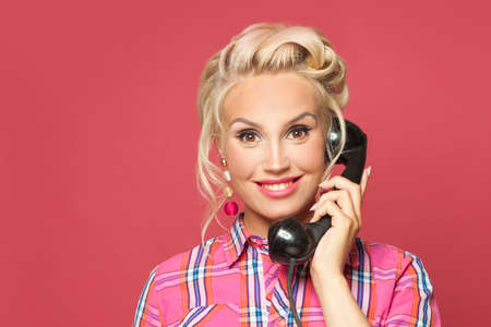 Beautiful pinup woman answers a phone call on red background