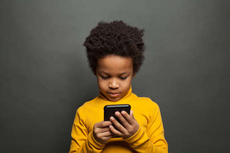 Little black child using smartphone