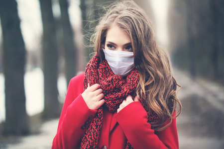 Beautiful woman in medical protective face mask outdoors