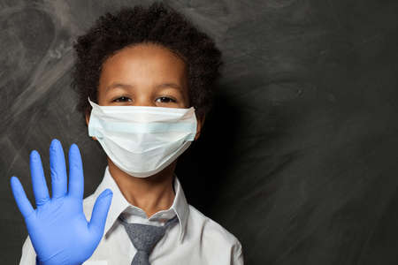 Smart black child in protective medical face mask showing stop gesture Stock fotó