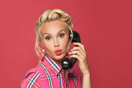 Happy pinup woman phone. Beautiful retro model girl with red lips makeup and vintage old-fashion hairstyle