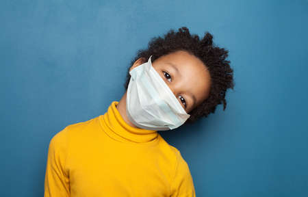 Black child in medical protective face mask on blue background Stock fotó
