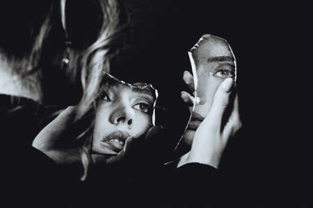 Lovely woman looking at broken self-image mirror, black and white retro portrait