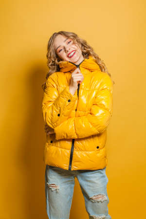 Attractive woman in season down jacket on bright yellow background Stock fotó