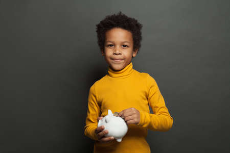 Smart black child with money box and coin