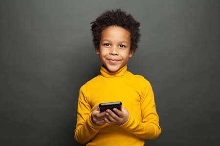 Happy African American child using smartphone