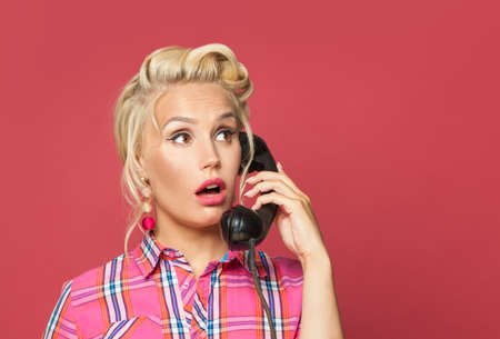 Shocked pinup woman phone. Beautiful retro girl with red lips makeup and old fashion hairstyle